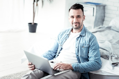 Positive delighted male leaning on bed and using his laptop while typing message