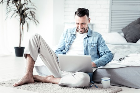 Smile and do. Delighted brunette male expressing positivity while using his gadget and sitting on the floor