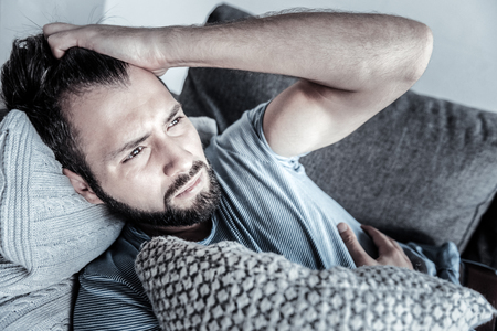 Think about changes. Handsome male pressing lips and thinking about problems while lying on his sofa Foto de archivo