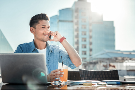 Positive conversation. Confident brunette keeping smile on his face and holding telephone while having pleasant conversation
