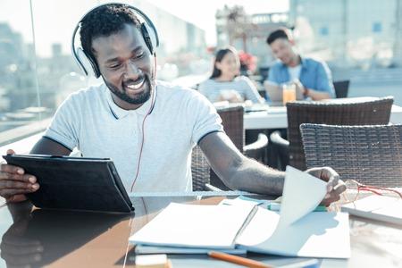 Hombre sonriente leyendo notas. Feliz joven expresando positividad y girando la cabeza mientras mira notas