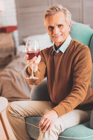Caring man. Loving caring man feeling memorable while giving glass of wine to his beautiful wife Banco de Imagens