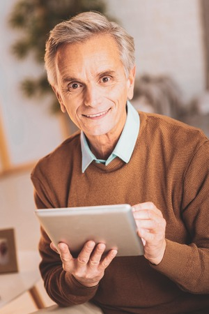 Shopping online. Aged modern man feeling rather inspired while shopping online on his new tablet Stock Photo