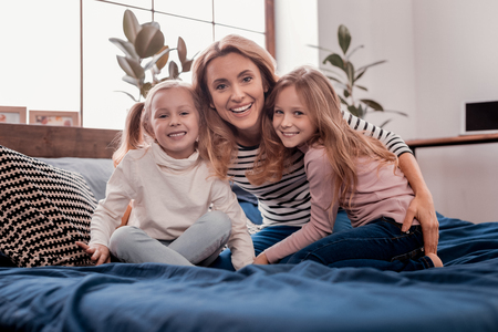 Family issues. Children and mother smiling while looking at you Stock Photo