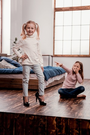 Stylish kids. Fashionable cute children posing while trying new mothers high heels