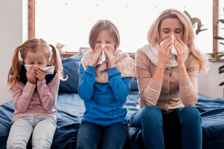 Dont catch a cold. Sick family sitting on the bed while sneezing