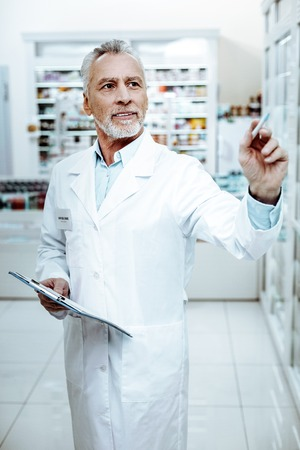 Pills review. Pleased mature male person holding folder in right hand while checking amount of goods