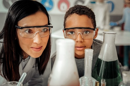 Pleased boy wearing protective glasses while having lesson in laboratory