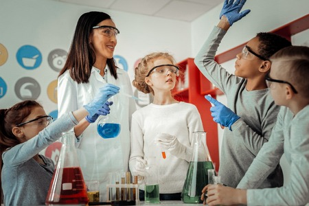 Attentive blonde girl standing near her teacher while helping to do experiment Banco de Imagens