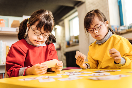 Dark-eyed twins. Dark-eyed twins with genetic disorder sitting at the table and playing with cards together Foto de archivo