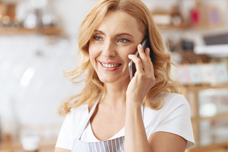 The order will be delivered in several minutes. Portrait of a cheerful woman listening attentively to her client while talking with him on phone and taking an order from him.