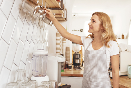 Relaxed atmosphere. Side view on a cheerful mature lady smiling while working in a local cafe and taking a metal cup for a warm aromatic drink.