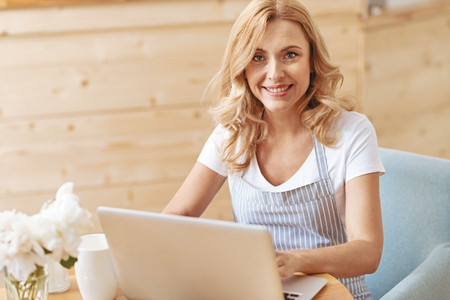Positivity is the to success. Cheerful woman looking into the camera with a friendly smile on her face while sitting at a laptop and enjoying her work at a cafe,