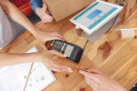 Fast and easy payment. Top view on a female client giving her credit card to a cashier while standing in a shop and paying for her purchase. Banco de Imagens