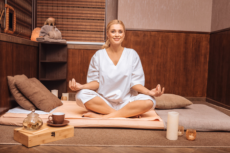 Pleasant mindfulness. Positive relaxed woman smiling to you while sitting in the lotus pose