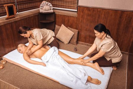 Piccoli piaceri. Bella donna di bell'aspetto che fa un massaggio mentre visita un centro benessere?