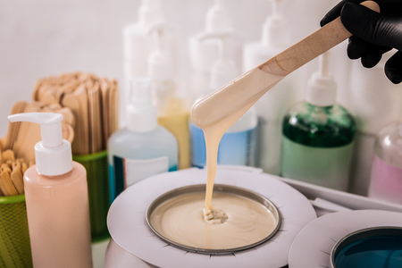 Wax ready. Experienced master in hair removal preparing wax before removing hair of her client Archivio Fotografico