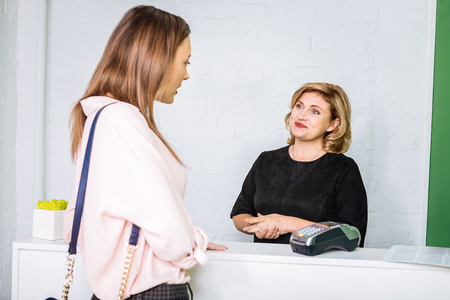 Asking about services. Appealing stylish businesswoman asking about some services coming to beauty salon