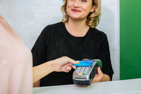 Smiling worker. Blonde-haired worker of beauty salon smiling while contacting with client paying by card Banque d'images