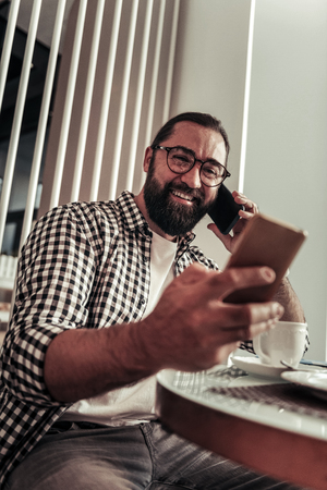 Digital technology. Happy bearded man looking at the smartphone screen while talking on the phone Foto de archivo