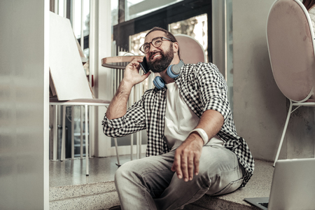 In touch. Delighted bearded man putting a phone to his ear while making a call