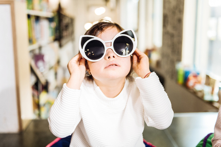 Fun with sunglasses. Funny little dark-haired girl with Down syndrome having fun with sunglasses Banque d'images