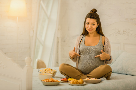 Eating a lot while pregnant. The pregnant woman eating a lot of different food Stock fotó