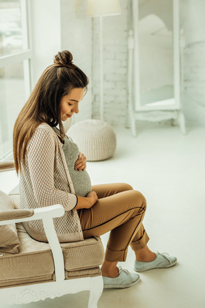 Future motherhood. The young pregnant woman sitting in the armchair