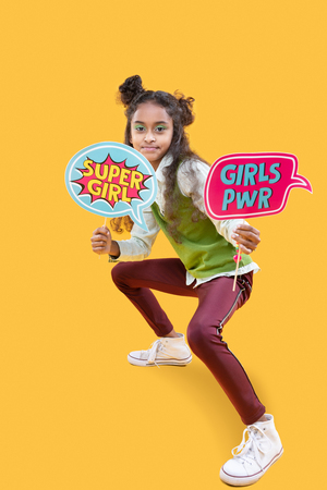 I am a super girl. Nice pleasant girl holding colorful signs while standing against yellow background Stock Photo