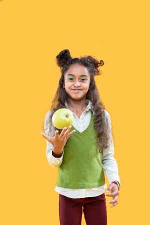 So healthy. Delighted happy girl holding a green apple while wanting to eat it
