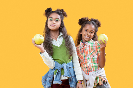 Delicious apples. Nice happy girls smiling while showing you delicious food Stock Photo