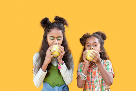 Healthy nutrition. Nice hungry girls standing together while eating tasty green apples