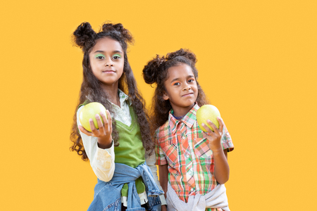 Healthy nutrition. Cute beautiful girls looking at you while showing what they eat