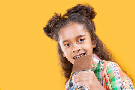 Sweets lover. Joyful pleasant girl smiling while enjoying her sweet chocolate