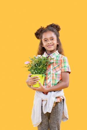 Beautiful plant. Cheerful delighted girl smiling to you while holding her favourite flower Stock Photo