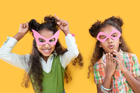So much fun. Joyful nice girls smiling while wearing pink masks Stock Photo