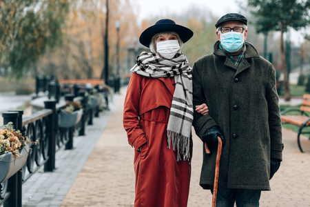 Preventive measures. Charming woman wearing stylish hat while walking in park with her husband