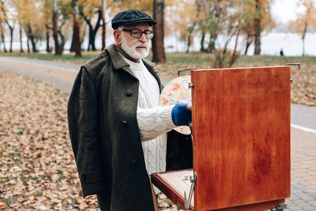 Mature artist. Kind pensioner enjoying his hobby, looking at working process Фото со стока