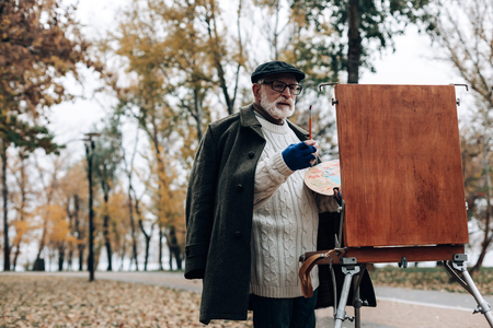 Landscape artist. Concentrated male person looking at easel while working at his project