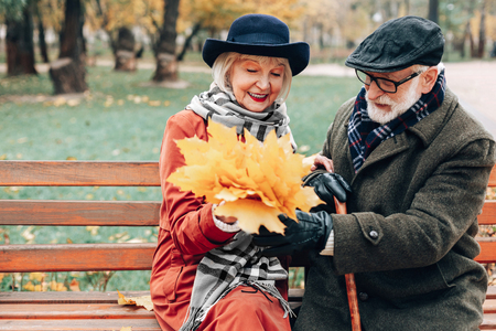 Autumn bouquet. Cheerful senior female keeping smile on her face while taking present from partner