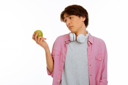 On a diet. Sad cheerless boy looking at the apple while not wanting to eat it Stock Photo