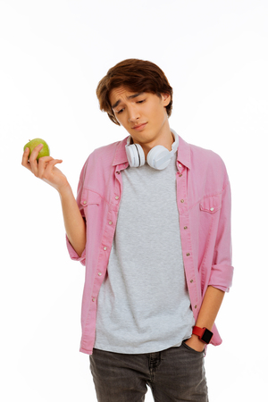 Young teenager. Nice bored boy putting a hand in his pocket while holding an apple