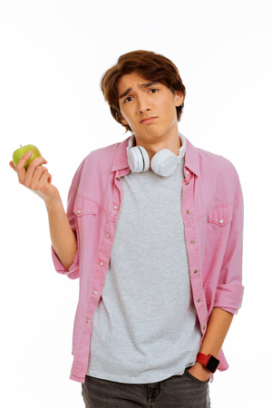 Expression of emotions. Pleasant nice teenage boy looking at you while holding an apple in his hands Stock Photo