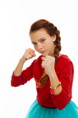 Real tomboy. Nice serious girl holding her fists while being ready to fight