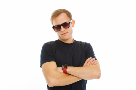 Confident man. Good looking confident man standing cross handed while looking at you through sunglasses