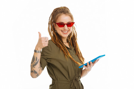 All is perfect. Delighted pleasant woman showing thumbs up gesture while holding her tablet Stock Photo
