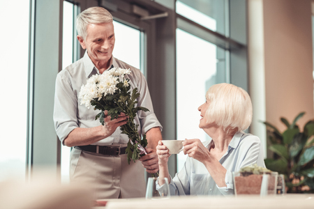 Young again. Smiling happy lady receiving flowers from a man while sitting in a cafe