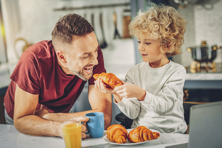 One bite. Handsome vigorous man biting and boy holding croissant