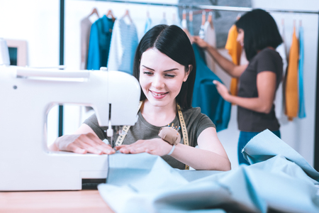 New order. Talented hardworking seamstress sewing a dress working with sewing machine Imagens - 115430306