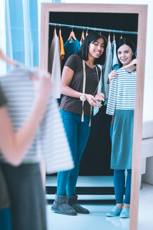 Pretty girl trying on a dress and her friend helping her